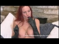 Busty red head Faye rubs her pussy with her leathe...