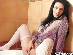 Brunette milf peeing into the bath tub